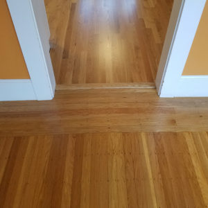 After - The newly finished dining room floor at the top with the old faded floor in the living room